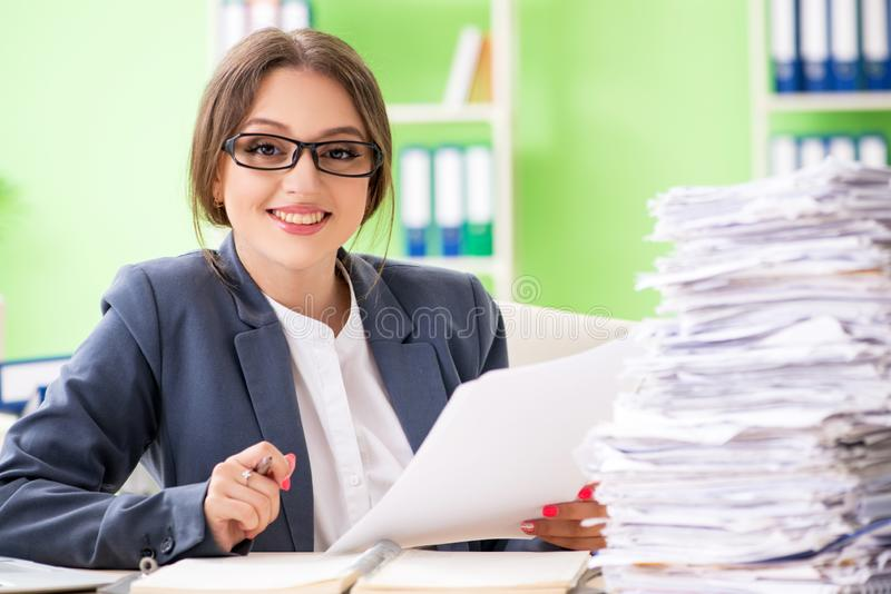 The young female employee very busy with ongoing paperwork stock photos