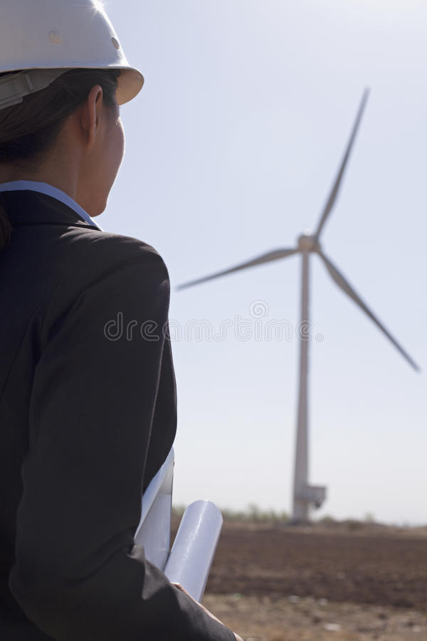Young female engineer holding blueprints and checking wind turbines on site, rear view royalty free stock images