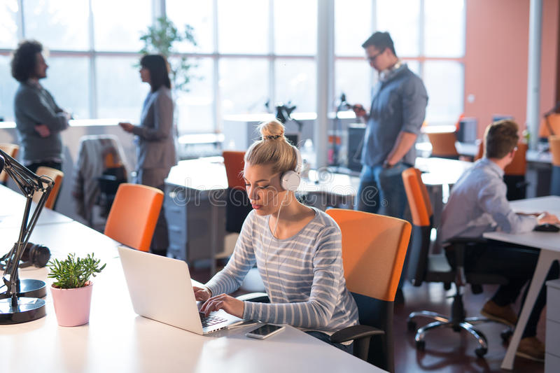 Businesswoman using a laptop in startup office stock photo