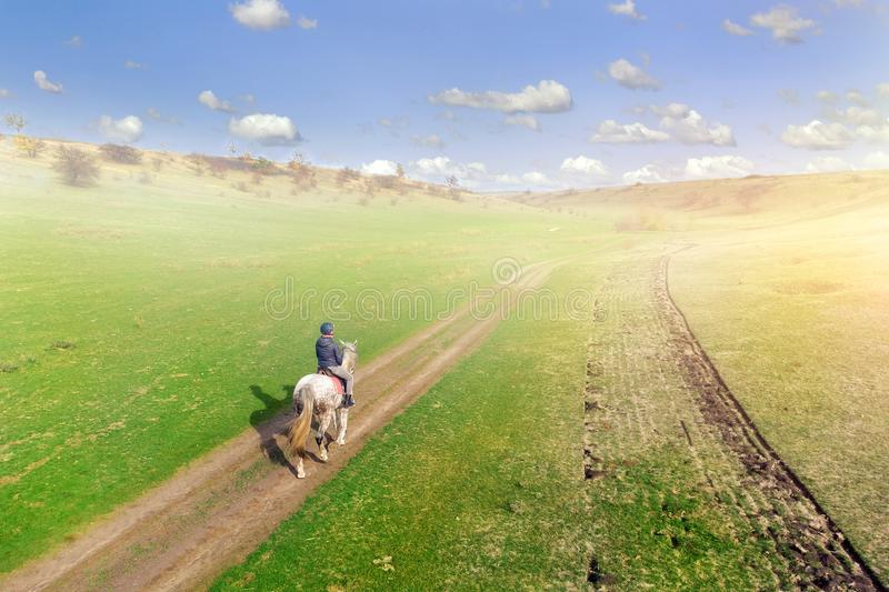 Young female equestrian riding horse along rural countryside. Rider on horseback going through green hillside.Travelling along. royalty free stock photos