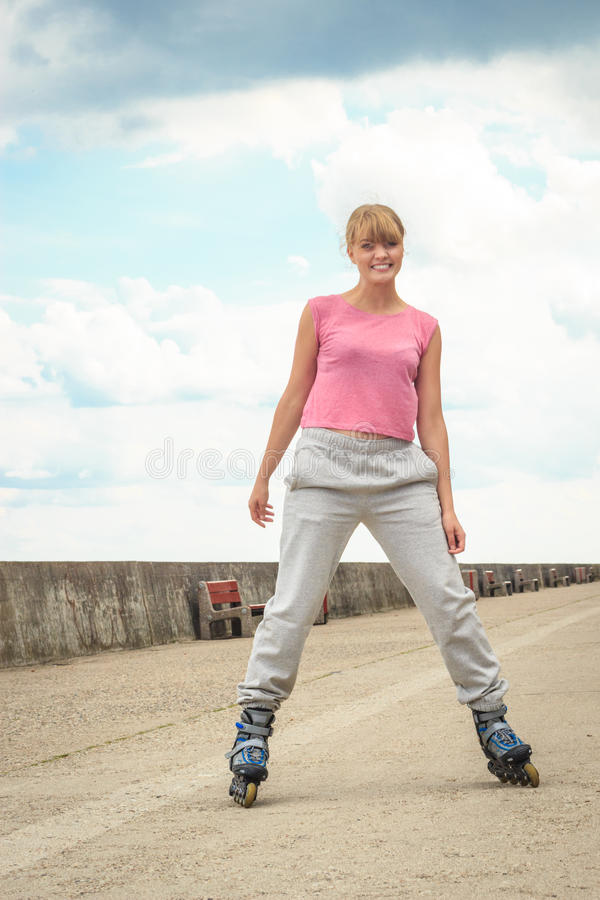 Young female exercise outdoors ride on rollerblades. stock image