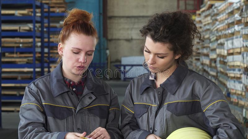 Female factory workers examining documents together at the storage. Young female factory workers checking stock doing paperwork at the factory warehouse royalty free stock photos
