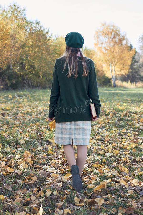 Young female with fall autumn leaves and red book in the hands in vintage old style clothes walking outdoors in the park royalty free stock photos