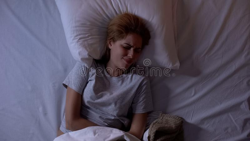 Young female feeling strong abdominal pain lying in bed, having menstrual period royalty free stock image