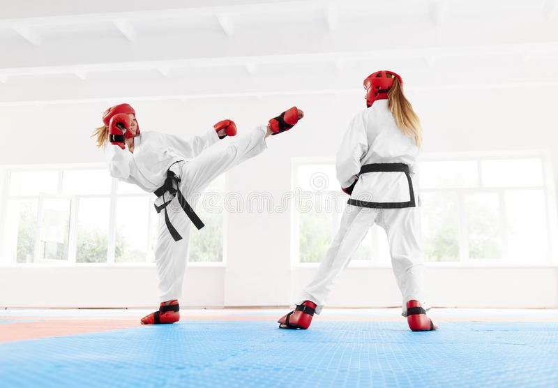 Young female fighter boxing using karate technique kick and punch. stock image