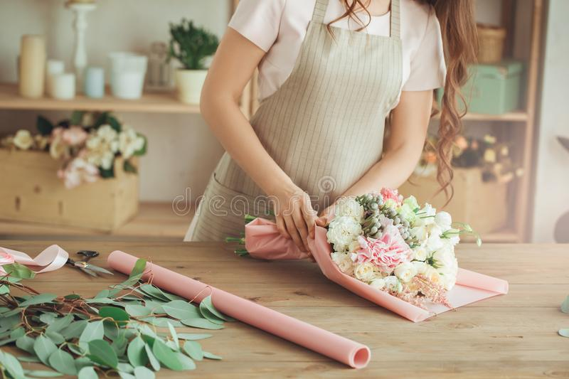 Young woman florist occupation working with flowers. Young female florist working with flowers gift paper stock photo