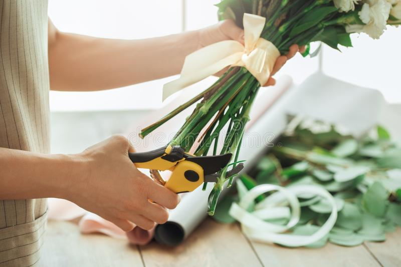 Young woman florist occupation working with flowers. Young female florist working with flowers making bouquet royalty free stock photo
