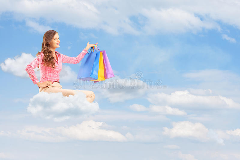 Download Young Female Flying On Cloud And Holding Bags Against Cloudy Sky Stock Image - Image: 33328895