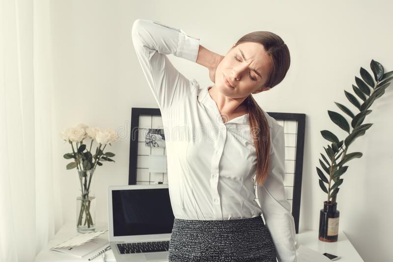 Young woman freelancer indoors home office concept formal style muscle pain stock photography