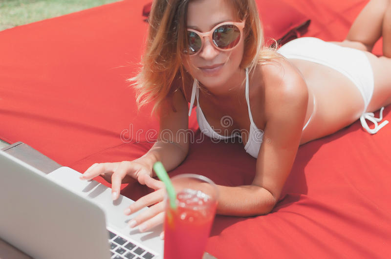 Young female freelancer laying near the pool and working on her laptop. royalty free stock images