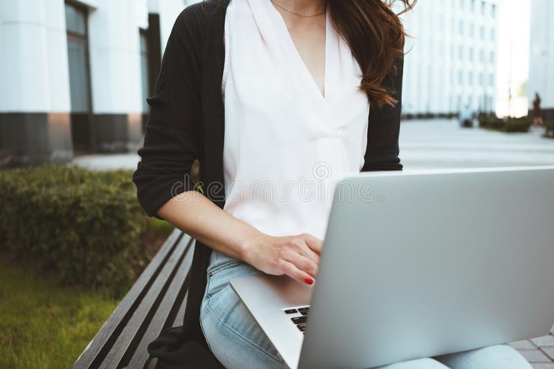 Young female freelancer making labor market research on modern laptop, sits on outdoors in urban street. Woman student work on mobile computer royalty free stock images