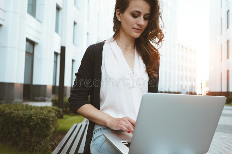 Young female freelancer making labor market research on modern laptop, sits on outdoors in urban street. Woman student work on mob. Ile computer. Flare effect royalty free stock photography