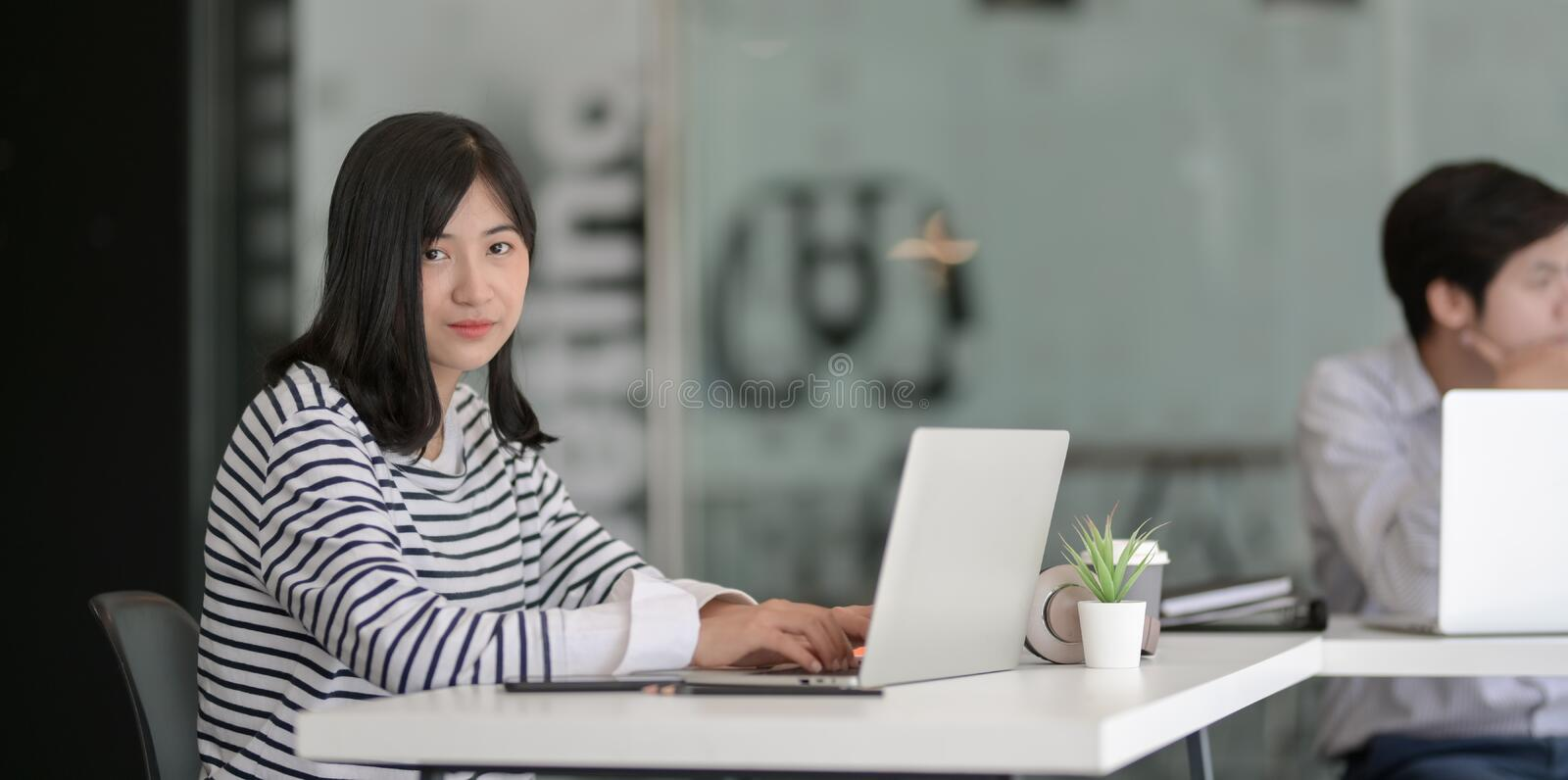 Young female freelancer working on her project with laptop computer and smiling to camera stock images