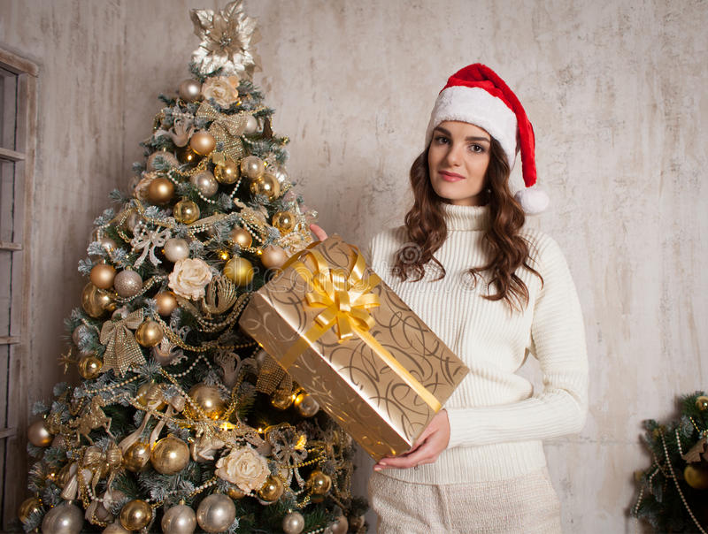 Young female with gift box near Christmas tree in cosiness home. Young attractive brunette woman with gift box near Christmas tree in cosiness home interior stock images