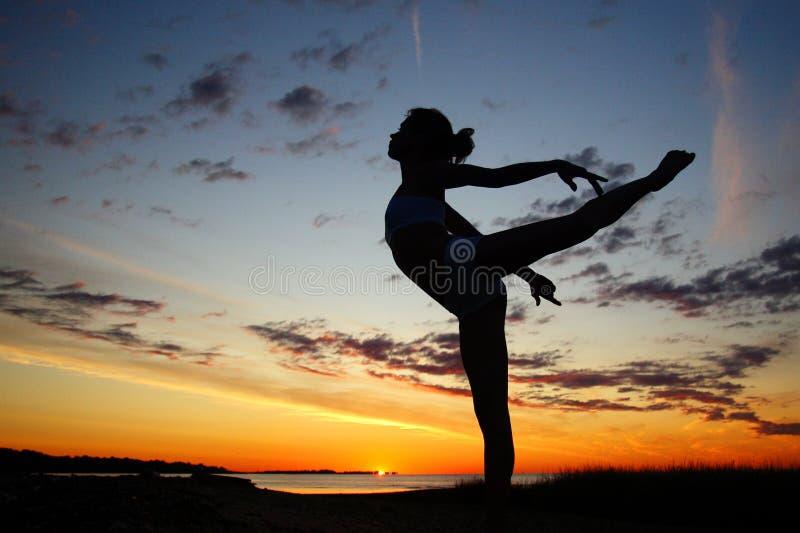Young female gymnast exercising at sunrise stock images