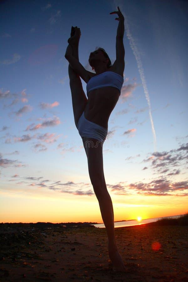 Young female gymnast exercising at sunrise stock image