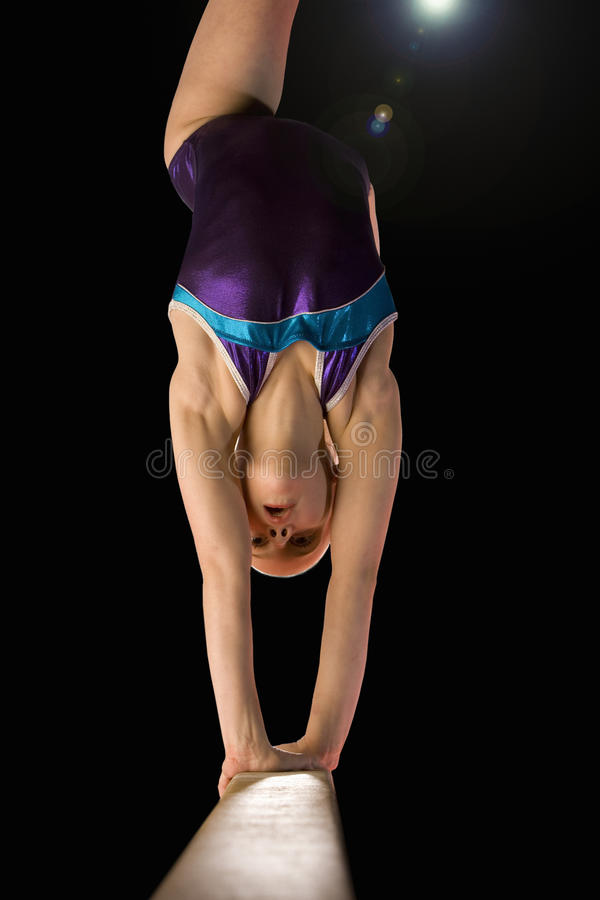 Young female (10-12) gymnast performing on balance beam, low angle view (lens flare) stock images