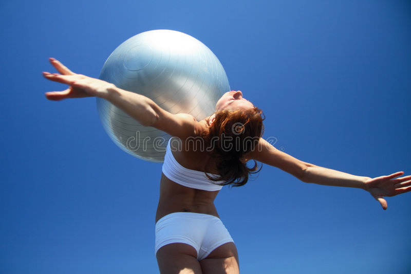 Young female gymnast with yoga ball on her chest royalty free stock photo