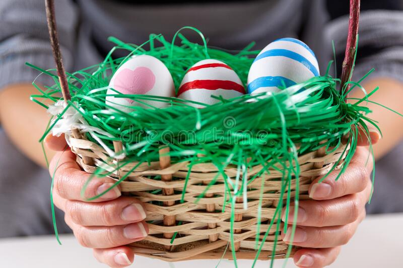 Girl hands with Easter colorful eggs in a wooden basket with green grass royalty free stock photography