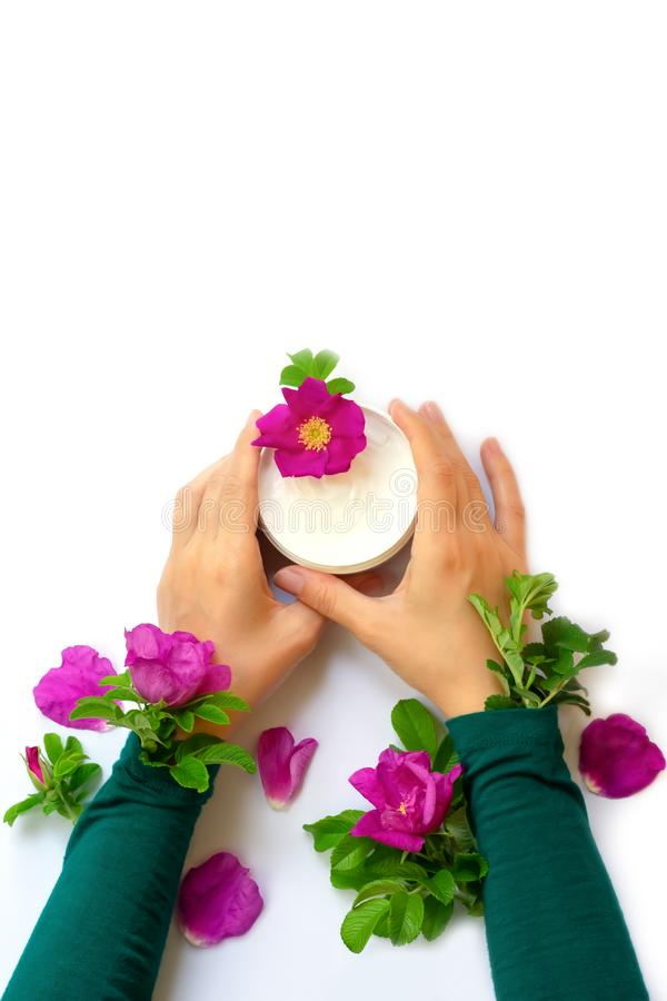 Young female hands are holding jar with white anti-ageing moisturizing cream with dog rose oil essential and vitamin E royalty free stock image