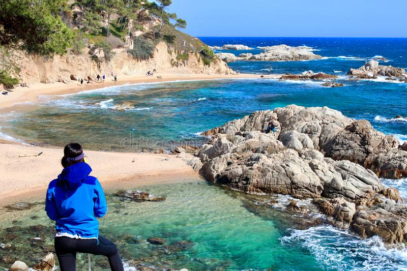 A young female hiker looking an amazing landscape in `Cala Estreta` beach, la Costa Brava, Catalonia, Spaon. stock photography
