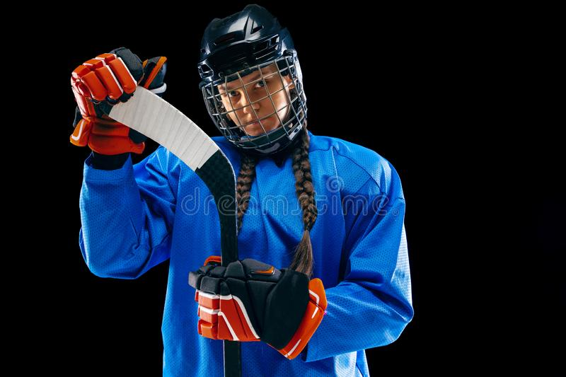 Young female hockey player with the stick isolated on black background royalty free stock image