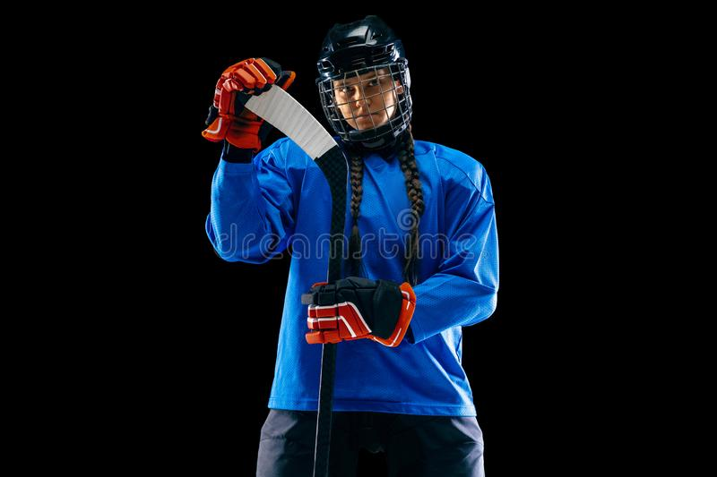 Young female hockey player with the stick isolated on black background stock images
