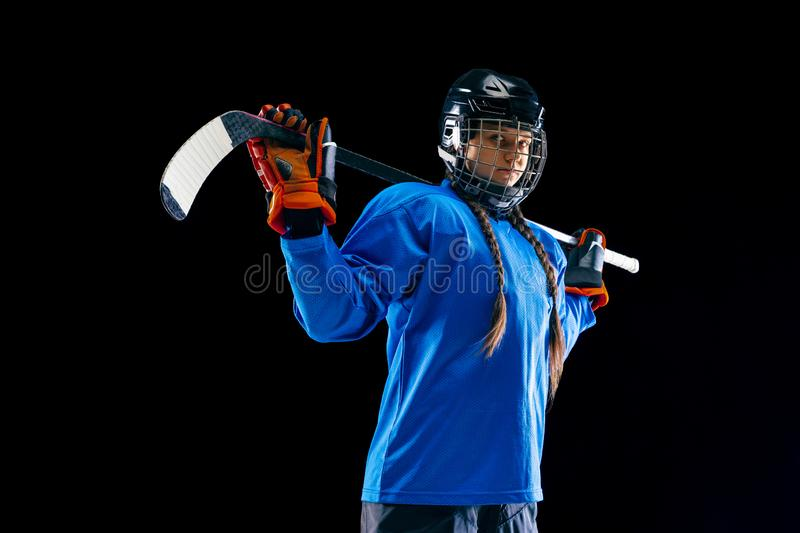Young female hockey player with the stick isolated on black background royalty free stock photo