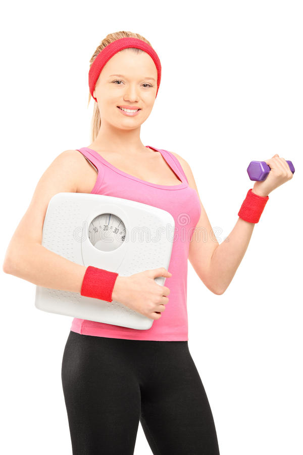 Young Female Holding A Dumbbell And A Weigth Scale Royalty Free Stock Photography