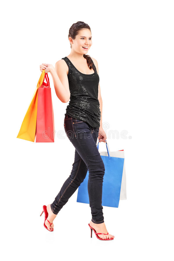 Download Young Female Holding Shopping Bags And Walking Stock Photo - Image: 26101202