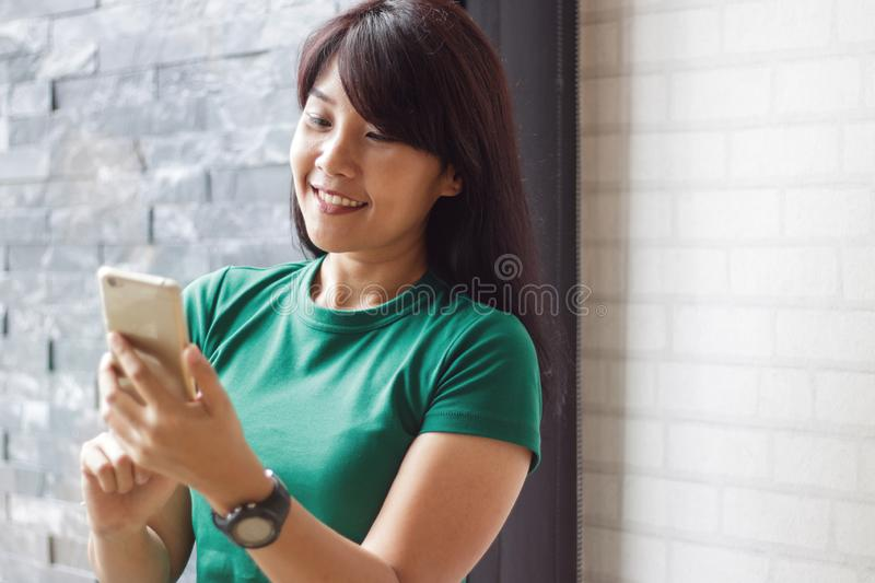 Young female holding smartphone and reading content in social network. Copy space, Selective focus. stock images