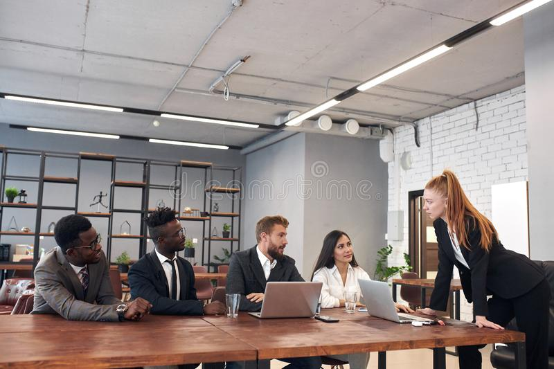 Young female international team coach mentor speaking at diverse corporate group meeting. Side view on beautiful women with red hair, team leader coach mentor stock photography