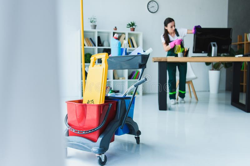 young female janitor cleaning office with various stock photo