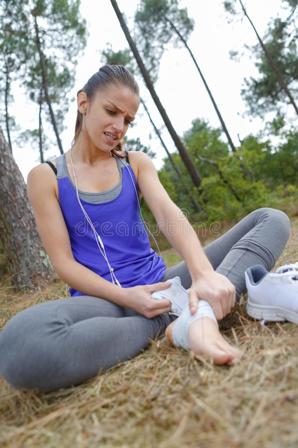 Young female jogger having pain in leg at park stock photo