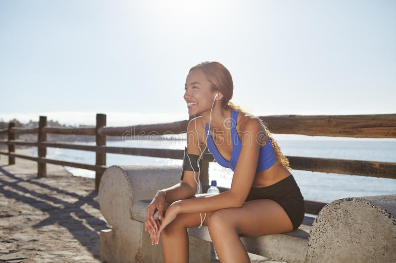 Young female jogger resting on the coastline royalty free stock images