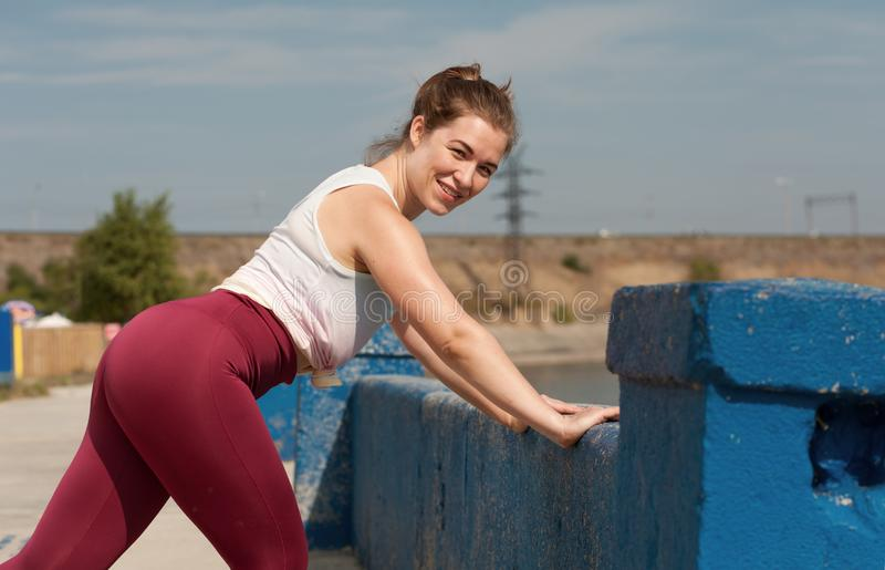 Young female jogger warmimg up stock images