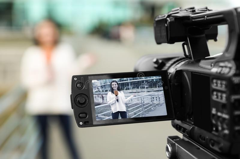 Young female journalist with microphone working on street, focus on camera display stock image
