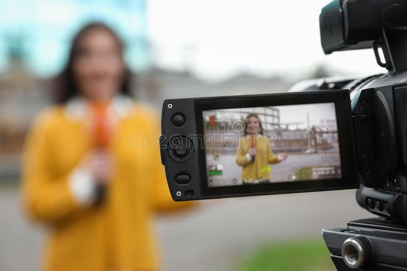 Young female journalist with microphone working on street, focus on camera display stock photos