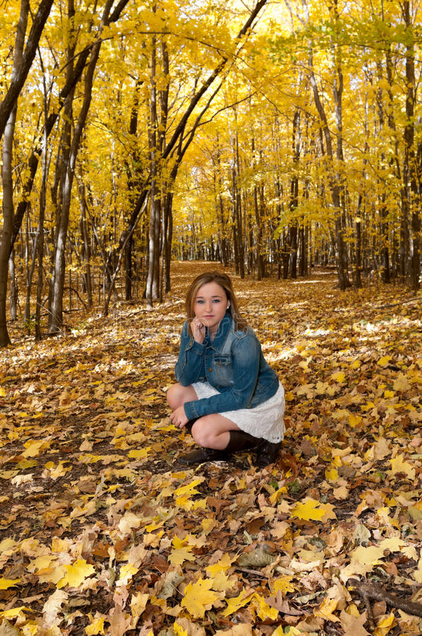 Young Female Kneeling on Forest Trail stock photo