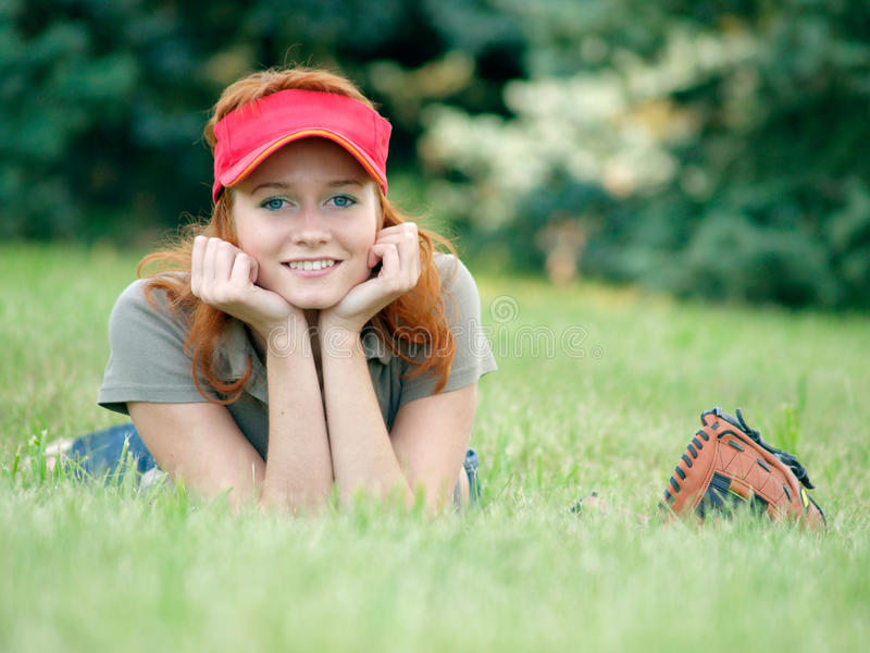 Young female laying on the gras with mitts. stock image