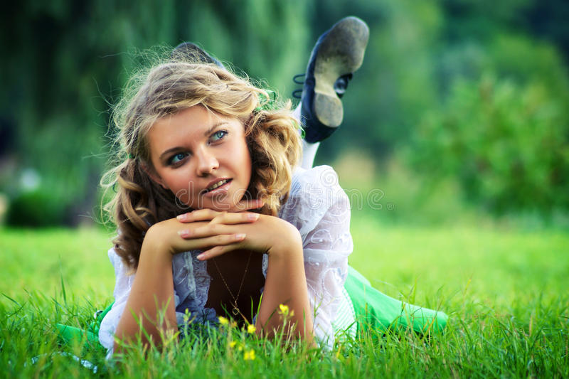 YOUNG FEMALE LAYS ON THE GRASS stock photography