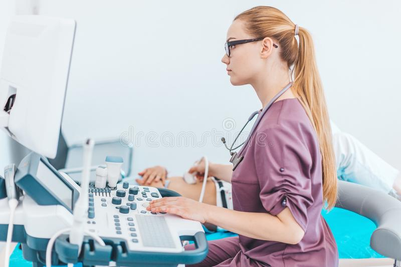 Young female blonde doctor with black glasses. Ultrasound scanner in the hands of a doctor. Diagnostics. Sonography royalty free stock photo