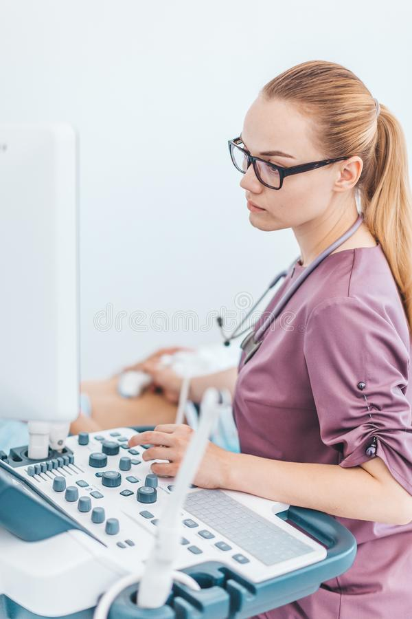 Young female londe doctor with black glasses. Ultrasound scanner in the hands of a doctor. Diagnostics. Sonography. royalty free stock photos