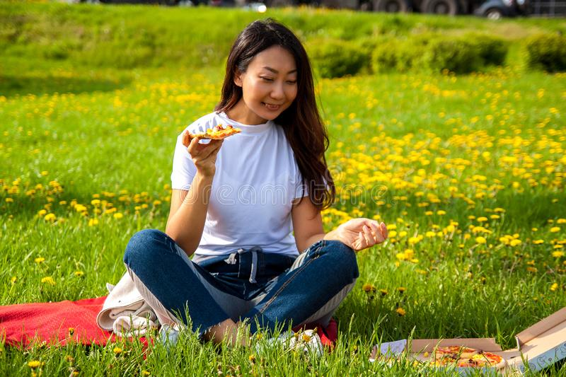 Young female with long hair holding slice of pizza while sitting on grass and enjoying lunch. Young asian female with long hair holding slice of pizza while stock image
