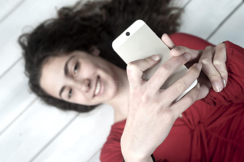 Young female lying on floor taking selfie stock photos