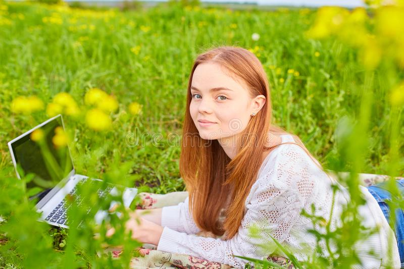 Smiling girl with laptop on grass royalty free stock image