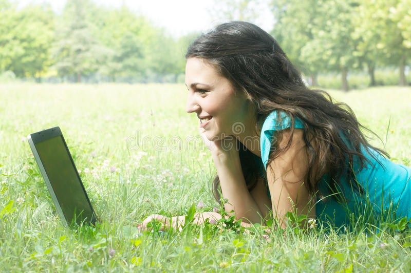 Young female lying on the grass using a laptop royalty free stock image