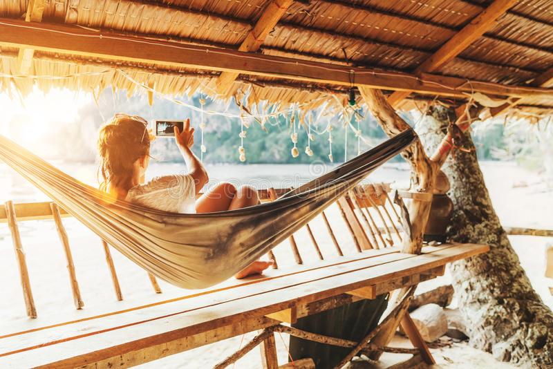 Young female lying in hammock and taking a landscape photo using modern smartphone on Samui island in Thailand. Careless stock image
