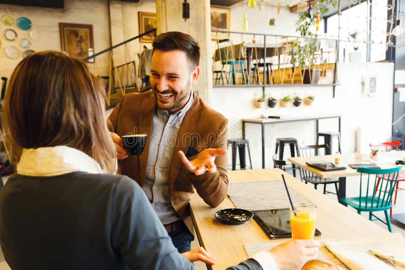 Young female and male business partners enjoying their coffee break during a busy work day stock images