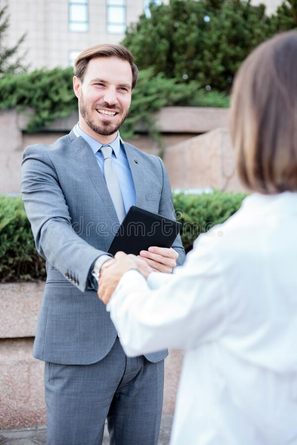 Young female and male business partners shaking hands after a successful meeting in front of an office building. Young female and male businesspeople shaking stock photography